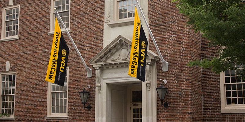 A photo of the front of the Medical College of Virginia campus library with the words Tompkins-McCaw Library engraved over the door with flags of black and gold with Tompkins-McCaw Library.