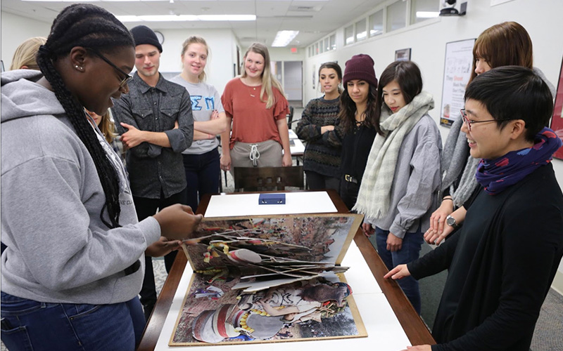 Andrea Kohashi leading a Special Collections and Archives class with an art book on the table.