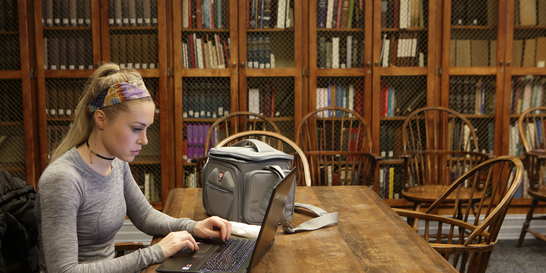 Woman sitting at a table on her laptop in the Tompkins-McCaw Reading Room.